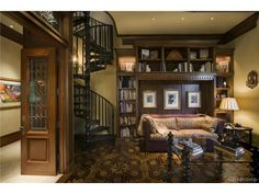 A massive and grand home library with dark wood, built in shelves, and a spiral staircase. Coldwell Banker