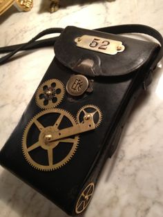"""Here's an iGearz Steampunk """"Adventure Case."""" This medium sized black leather case is made using an antique Eastman Kodak Corp. camera case from around 1914, then brass gears, clock parts, and a metal number plate """"52"""" are added, the inside is fully hand lined in premium red felt with a gold cord trim, and a new black leather adjustable carry strap is put on. This medium size case is perfect for carrying around your cell phone, wallet, etc on your next adventure!"""