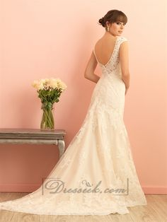 This sweet cap sleeved lace gown is features a scooped, transparent lace back.