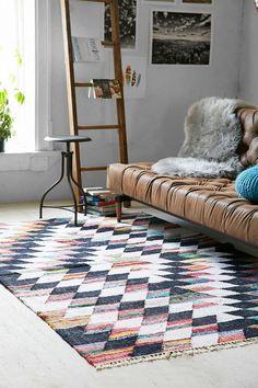 tapis nordique à motifs graphiques, canapé en cuir et échelle de rangement en bois