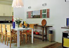 Esta sala de jantar, decorada pelo arquiteto Matheus Ribeiro, mistura estilos. Tem mesa branca, com linhas retas, e cadeiras Célia, dos Irmãos Campana. A queijeira serve de aparador e o piso é de tecnocimento  Marcelo Magnani / Casa e Jardim