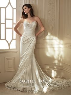 Sophia Tolli - Y11642 – Morrigan - Strapless asymmetrically draped shimmer satin fit and flare wedding gown with sweetheart notched neckline and modesty panel, hand-beaded lace appliqué empire bodice, scalloped lace asymmetrically trims front skirt, scalloped hem lace extends past satin onto chapel length train, semi sheer back bodice with corset. Removable spaghetti and halter straps included.  Sizes: 0 – 28  Colors: Ivory, White