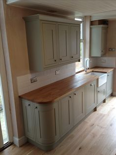 Sage green kitchen (Benchmarx range) with treated oak work surface and Belfast sink. Victorian tiles laid in a brick bond make for a stunning classic look.