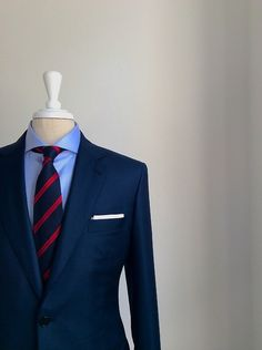 Navy suit paired with navy & red striped tie, sky blue shirt, and white pocket square.
