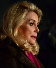 French actress Catherine Deneuve signs autographs as she arrived for a photocall ahead of the Cinema for Peace Gala 2017 on February 12, 2017 in Berlin. / AFP / John MACDOUGALL