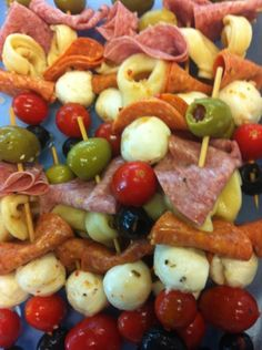 antipasto on a stick -- marinated mozzarella, salami, black and green olives, cherry tomatoes and pepperoni.. looks like there's some cheese tortellini on there too. yumm-o