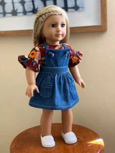 My daughter received an American Girl Doll for Christmas last year and I have been having so much fun sewing up little outfits for her. My five year old daughter loves being involved in the design process. We both agreed on a little denim pinafore dress and we love how it turned out. Best of all, I've provided the pattern as a free download plus a sew along tutorial for this post. Isn't it cute? #doll #diy #dress #pinafore #free #tutorial