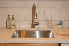 stainless sink, subway tile, white quartz countertops, gray grout