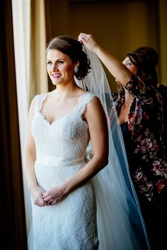 Morris Inn at Notre Dame getting ready - bride stands by window as her veil is fixed into her hair