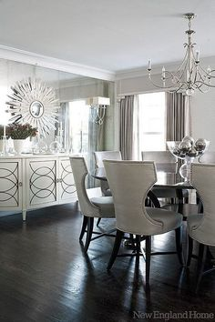 silver, grey, and off-white dining room with dark wood floors, a mirrored wall, and a sunburst mirror