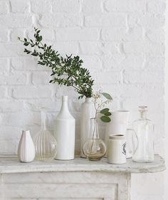 Who says vases need flowers? One sweeping spray of boxwood (tall) and a sprig of seeded eucalyptus (small) among a cluster of shapely vessels creates a festive moment on a mantel or in an entry. Stick with neutral-colored containers, and casually concentrate greens in the center.