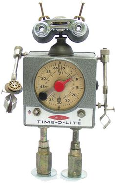 """Name: Hubert  D.O.B.: 9/29/08  Height: 13""""  Principal Components: Darkroom timer, binoculars, test tube clamps, oil can, hydraulic fittings, drawer knob, buttons"""