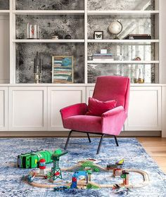 A hot pink velvet chair sits on a blue overdyed rug in front of white built-in cabinets fixed beneath styled white built-in shelves mounted to an antiqued mirrored backsplash.