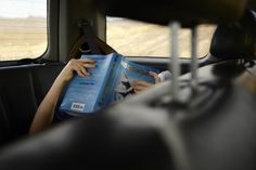 Teenager readying Hunger Games in the back of a car on a road trip.