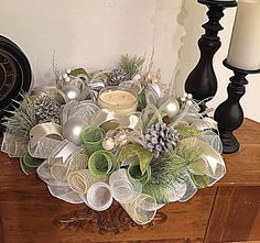 Decorate for Christmas with this elegant Pinecone silver white and moss candle arrangement.  It is made with high-quality silver white and moss metallic deco mesh.  There are beautiful Silver ornaments with frosted pine branches, flex tubing and white Christmas berries.  It shows with silky white, cream and moss ribbons and white washed pinecones.  This candle arrangement measures 20 inches and can ship out within 2 to 5 days of purchase.  Thank you for shopping with CK Dazzling Design.