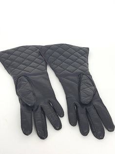 Chanel Rue Cambon quilted leather long gloves. They have a long Zipper with a Rue Cambon pull with telephone number and fax number etched in it. There is an adjustable snap which says Chanel Paris with 2 adjustments. The interior is burgandy quilted leather with silk at the fingers. There is a small leather pocket on the inside of both gloves.