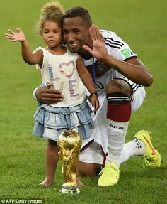 Jerome Boateng and his daughter pose by the trophy...
