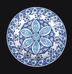 A RARE BLUE AND WHITE IZNIK DISH, TURKEY, CIRCA 1535-40 of rounded form with everted rim, the fritware body painted in blue and turquoise on a white ground with a central stylised rosette decorated with floral motifs, bordered by foliate stems, the rim with cintamani motifs between flowers, the exterior with a scrolling foliate design 37.8cm. diam.