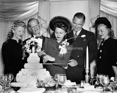 Phyllis Fraser, Radio editor and cousin of film actress Ginger Rogers, cuts her cake September 17, 1940 in New York after she was married to Bennett Cerf a New York Publisher. Ceremony was performed by New York Mayor Fiorello LaGuardia. Watching left to right are; Mrs. Lela Rogers, Ginger's mother; Gustave Cerf, Groom's father; Fraser; Cerf and actress Anne Shirley. Bennett Cerf, Ginger Rogers, Anne Shirley, September 17, Love Story, Editor, Groom, Father, Actresses