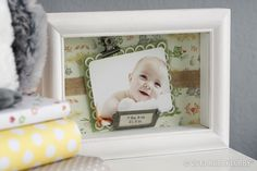 """Cute as a button! We embellished the back of this 8"""" x 6"""" shadow box frame with scrapbook paper and jute ribbon. Then we mounted the photo on two kinds of cardstock—the lacy border was made with a paper punch, and 3D adhesive makes the picture pop. Finishing touches: metal clip and metal nameplate."""