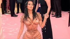 Kim Kardashian rocks the wet look at the 2019 Met Gala as she shows off her voluptuous figure in a stunning tight caramel gown. Kanye West stood by her side in a simple black tracksuit.