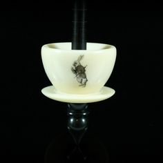 This Teacup spindle is made from alternative ivory and African blackwood, and on the whorl is an image of the White Rabbit, adapted from an original illustration from Alice in Wonderland.  It is 10 inches long and 1.23 oz.