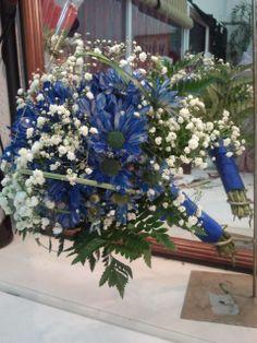 Vista frontal de un ramo de novia con margaritas azules, adornos de paniculata y adornos vegetales, con el mango tambien en tul azul a juego.