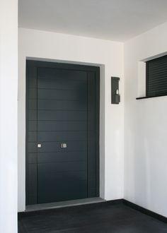Puerta exterior con estructura interna de pino y acabado en duelas de contrachapado marino lacado en color gris.