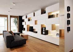 Interesante trabajo de decoración de un apartamento de 100m2 situado en Liubliana, con estanterías modulares, revestimientos de madera, y espejos.