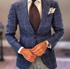 Blue window pane jacket, light grey trousers, white dress shirt, brown polka dots tie, white pocket square