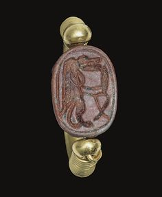 AN EGYPTIAN RED-GLAZED STEATITE SCARAB -  NEW KINGDOM, DYNASTY XVIII-XX, 1550-1070 B.C. The beetle summarily detailed, the underside with hippopotamus-headed Taweret, holding a knife before her, a sa-sign (protection) below, enclosed within a line border; mounted as a swivel ring in a modern gold setting.