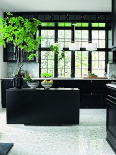 Beautiful kitchen with dark cabinetry and light flooring and counter-tops & walls.
