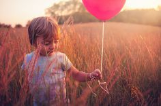 The Ward Debauche Family.  Little boy playing in fields of grass with a bright red balloon at sunset.
