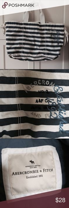 Abercrombie & Fitch large tote bag Large A&F tote bag, perfect for the beach and summer! Navy and white striped. Used only a few times, still in excellent condition! Able to cinch side of tote (where bow tie is). 1 pocket where inside logo is (3rd picture).  Approximately measures 22 x 12 x 5.5 inches. Abercrombie & Fitch Bags Totes