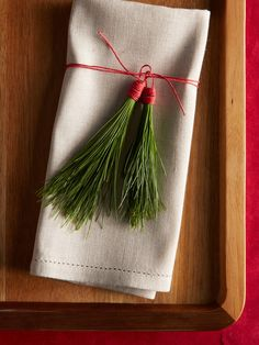 Linen napkins are a classic choice year-round. Make them special for the holidays with a little greenery via these easy-to-make pine needle tassels. All you need are pine needles and red twine.