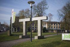 #Flensburg Ausgangspunkt der Skulptur von Max Bill ist nicht das Abbild klassischer Bauformen, sondern eine Konstruktion nach strengen mathematischen Regeln. Die Skulptur aus insgesamt 18 gleichen Elementen ordnet und gliedert den umgebenden Raum und lenkt die Besucher von der Straße zum Eingangsbereich.