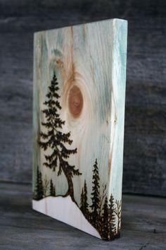 El árbol en este original arte de madera quemada parece ser mecida por la brisa alta en una ladera. Un nudo en la madera crea una característica interesante. Un luz azul/verde lavado realza la veta de la madera y crea un tono cálido hacia el cielo. Blanco se ha agregado un sentimiento invernales. Firmado y fechado en la parte posterior. Mide casi 8 3/4 pulgadas de alto por 5 1/2 pulgadas a través de 3/4 pulgadas de profundidad. Cuidadosamente envuelto y listo para enviar.