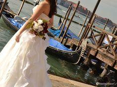 Un bouquet di rose rosse e bianche in mano alla sposa stanno ad indicare un…