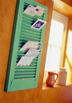 An old shutter makes a great mail sorter! It's also great for hanging jewelry or for use as a memo board with photos and notes tucked inside! #DIY #Memo_board #bulletin_board #shutter #upcycle #repurpose #reuse #jewelry #photo