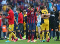 Gerard Pique of FC Barcelona looks dejected as Club Atletico de Madrid celebrate winning the La Liga after the match between FC Barcelona and Club Atletico de Madrid at Camp Nou on May 17, 2014 in Barcelona, Catalonia.