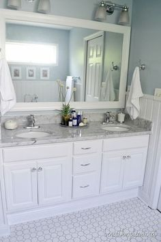Pretty Bathroom Makeover - raised the old vanity to a higher height, painted it white, marble countertop, framed mirror, wainscoating