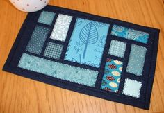 Ticker Tape Mug Rug (Quilt as You Go). Based on the ticker-tape quilt blocks this mug rug is perfect for any occasion and all tastes.  Here the ticker tape patches are set on navy linen.  But you could use holiday fabrics, florals, nautical prints - absolutely any design or collection you like.   I can see this pattern being used time and time again.