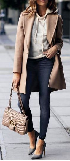 woman in gray top and blue jeans wearing gray coat and holding gray Guess tote bag. Pic by @london_style_blog