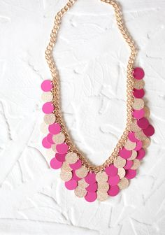 Delicate discs of pink and a textured gold color shimmer with the slightest of movements on this charming bib necklace. $10