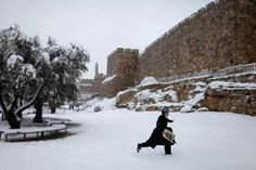 An Ultra Orthodox Jew wades through the snow next to the Old City walls in Jerusalem, during a snow storm  in the city, on 10 January 2013. The mid-East region has been gripped by a cold wave accompanied by heavy snowfalls since a few days. (Credit: EPA)