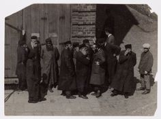 Lukow. 'A controversy.' A group of Jewish men in traditional dress stand by the corner of the 'besmedresh' (house of study and worship) as two men face each other in discussion.