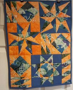 "Using up scrap blue and orange batik materials...has a variety of ""star"" blocks and filler blocks."