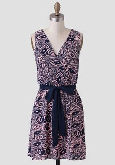 Designed with a flattering surplice neckline, this navy and pink dress features an allover abstract print with a solid navy sash.