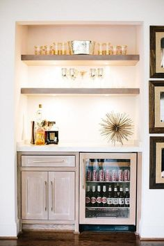 Mini bar nook is filled with gray wash floating shelves suspended over gray wash cabinets fitted with a glass front beverage fridge. Glass Shelves, Floating Shelves, Bar Shelves, Open Shelving, Shelves Lighting, Shelf Display, Wooden Shelves, Ikea Regal, Wet Bars