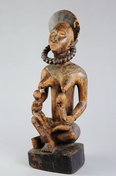 TYPE D'OBJET: Maternité. Statue anthropomorphe.   Appellations locales : Pfemba et Phemba.   ETHNIE: Yombe (Bayombe).   ORIGINE: République Démocratique du Congo. (ex Zaïre, ex Congo Belge).   MATÉRIAU(X): Bois, tissu.   DIMENSIONS: Hauteur 59.5 cm